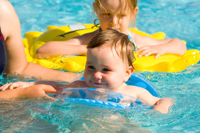 A happy baby attending a swimming lesson