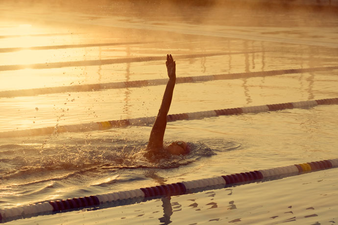 On a sunny morning, a young man swims backstroke in an outdoor pool while steam rises from the water.