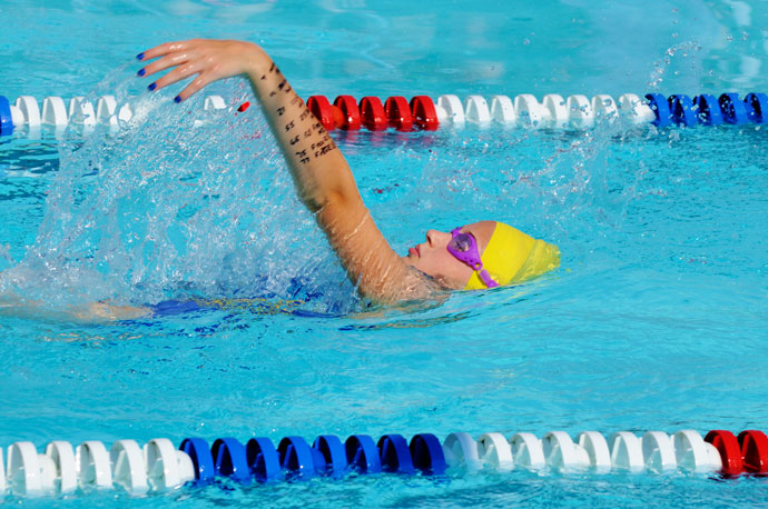 Picture of a female backstroke swimmer shot from the side above water in an outdoor pool.