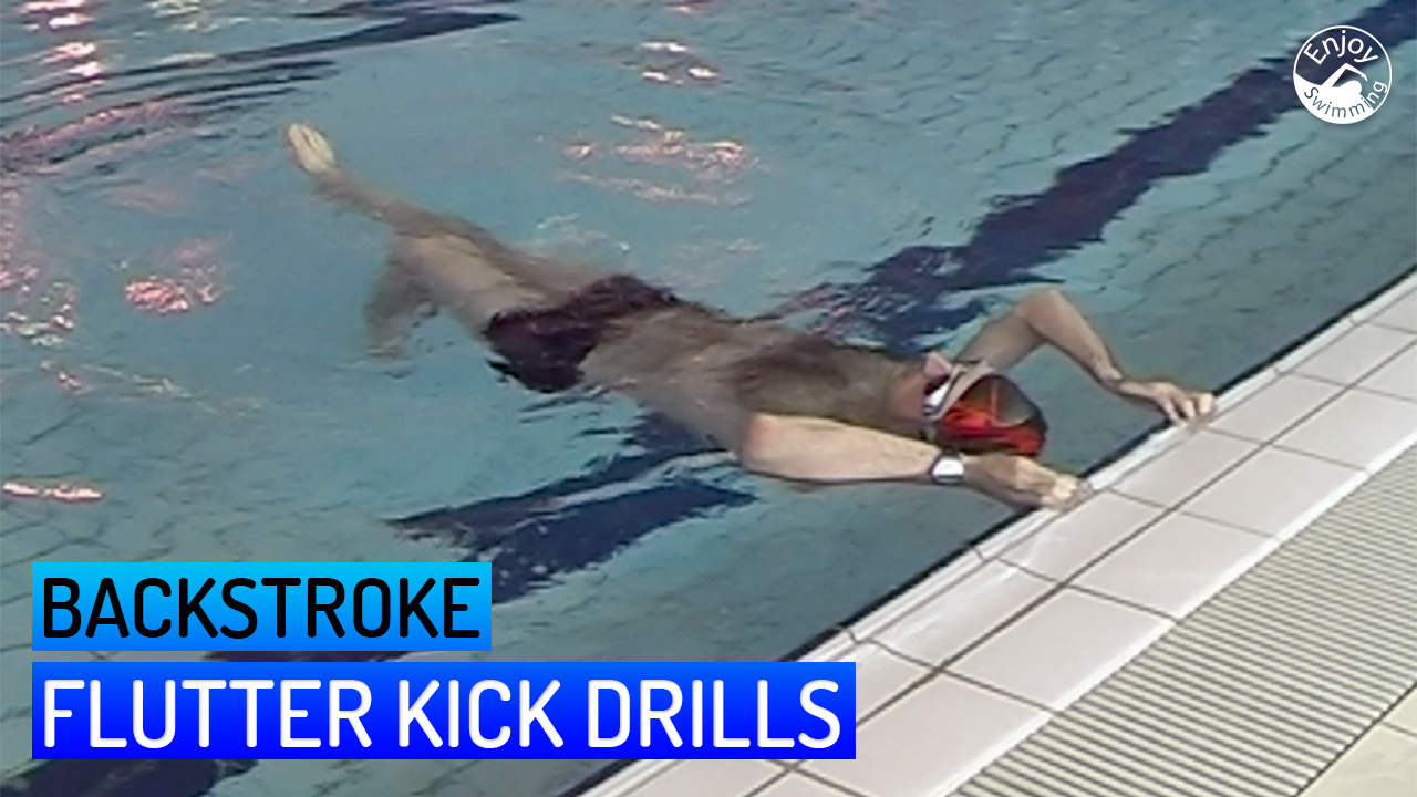 A novice swimmer practicing flutter kick drills for the backstroke.