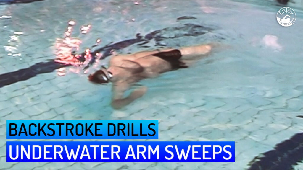 A novice swimmer who practices an underwater arm sweep drill for the backstroke.