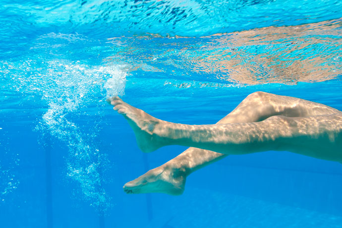Close-up of the legs of a backstroke swimmer.
