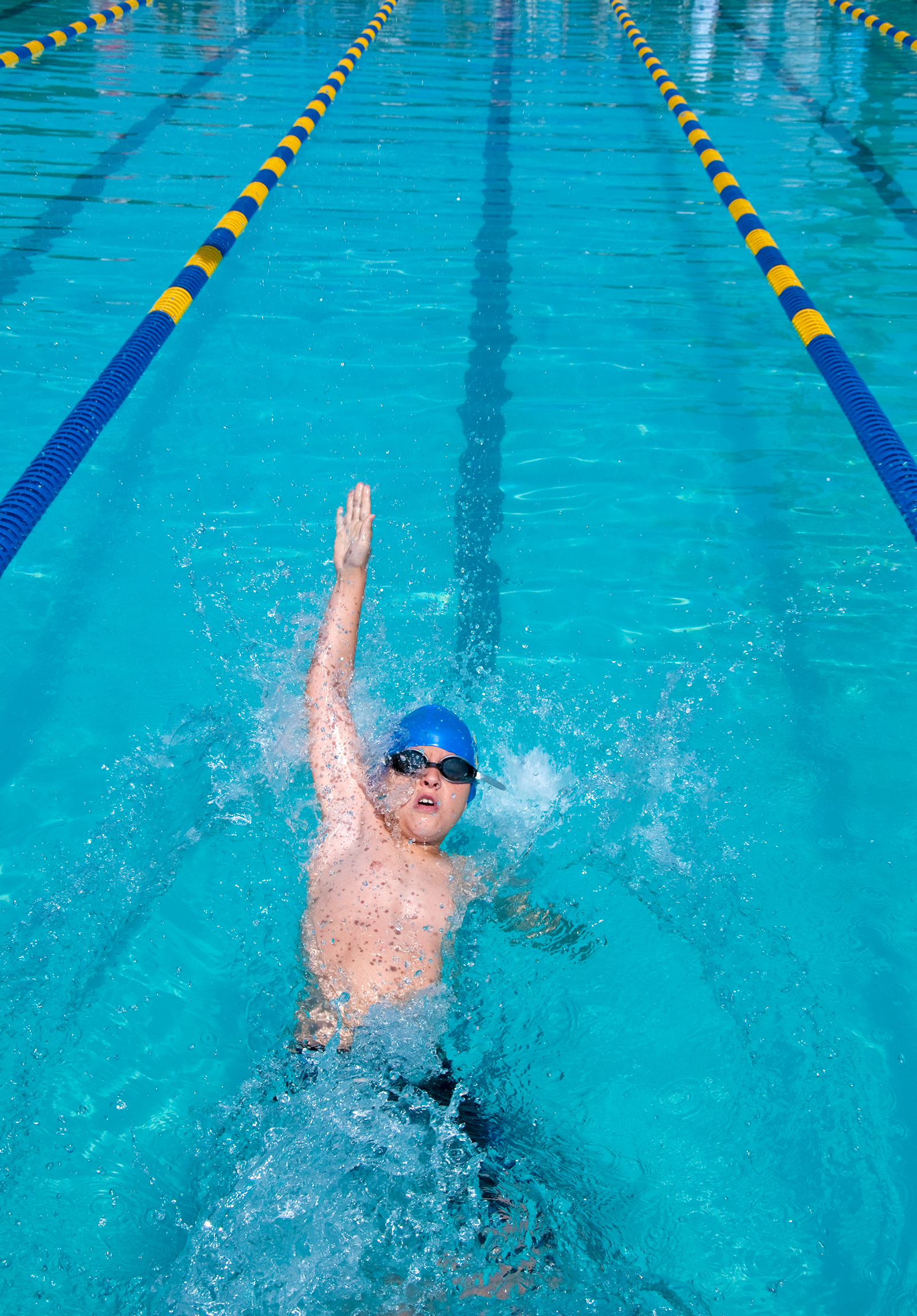 A young boy swimming backstroke
