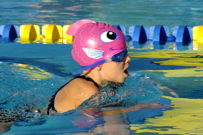 A young girl with a fish shaped pink swimming cap practices breaststroke.