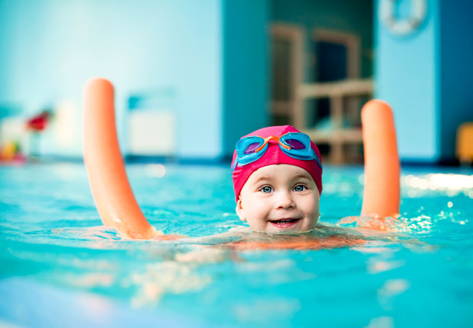 A smiling child learning to swim at the pool and using a swimming noddle for additional buoyancy.