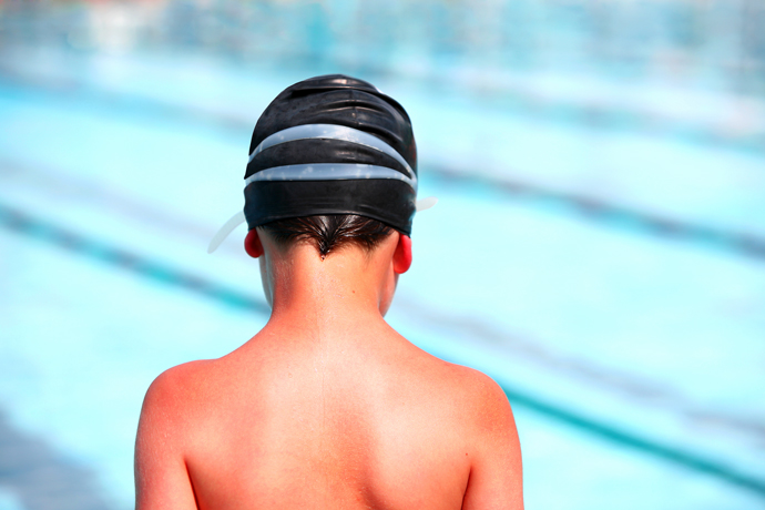A young boy swimmer with a sunburned back and shoulders
