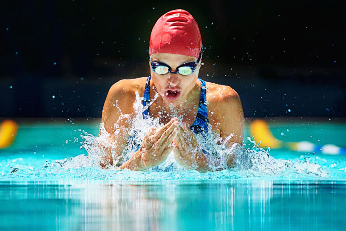 A young woman swimming breaststroke in an outdoor pool, as she is just inhaling.