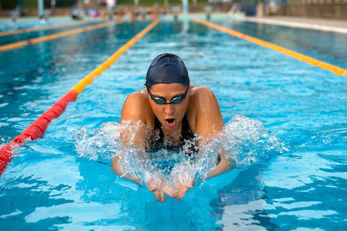 A woman who swims breaststroke in an outdoor pool