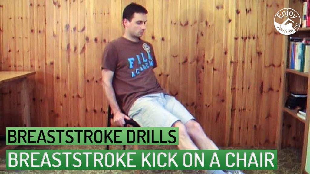 A swimming instructor demonstrates how to practice the breaststroke kick movements while sitting on a chair