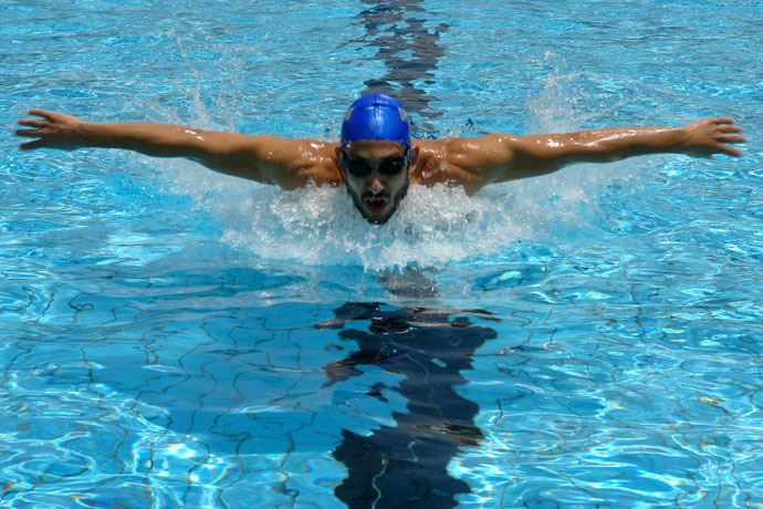 Picture of a young man swimming butterfly in an outdoor pool, with his arms extended sideways during the arm recovery above water.