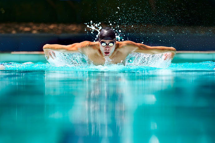 A young man swimming the butterfly stroke in an open pool on a sunny day.