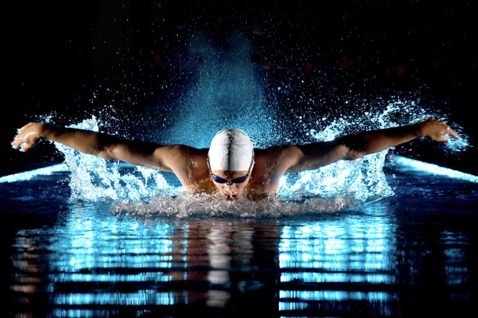 A butterfly swimmer shot at night in a pool
