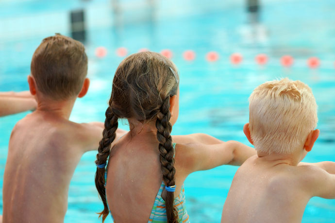 Three children practicing breaststroke movements on dry land