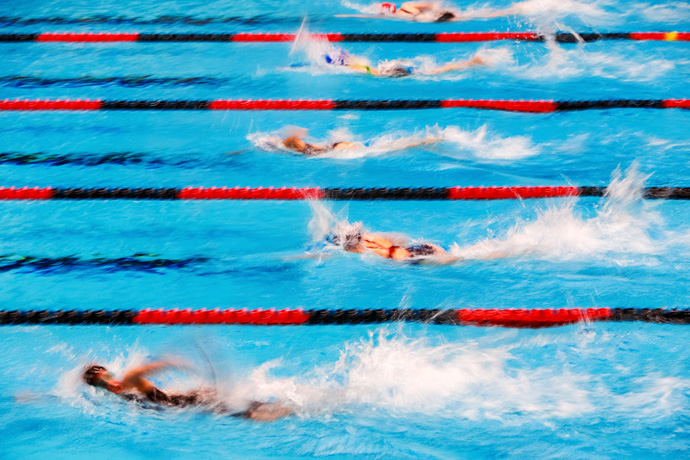 Swimmers using a powerful flutter kick in a freestyle swimming race