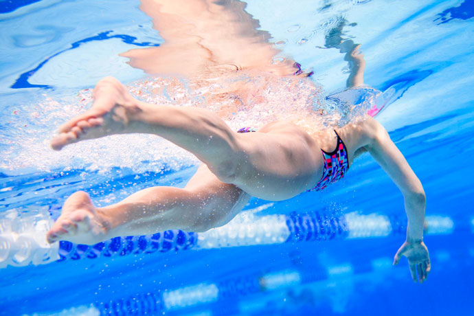 Underwater shot focused on the flutter kick of a front crawl swimmer