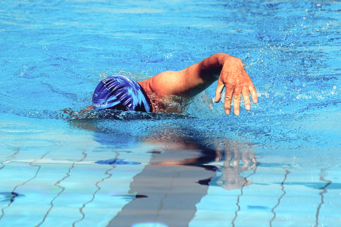 A front crawl swimmer with an overreaching arm recovery