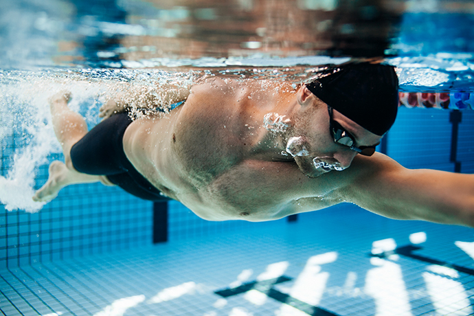 A freestyle swimmer exhaling underwater