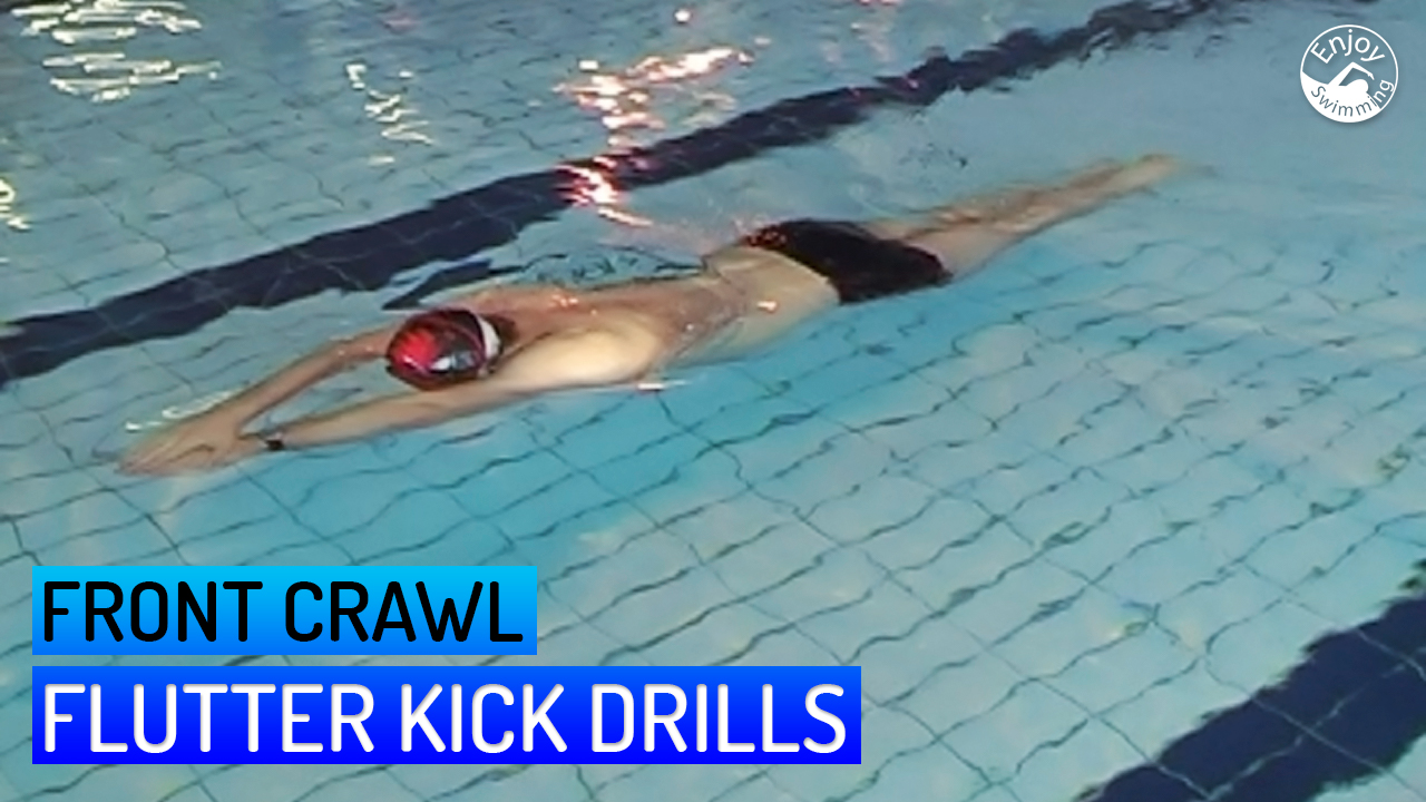 A front crawl swimmer who practices swimming drills for the flutter kick.