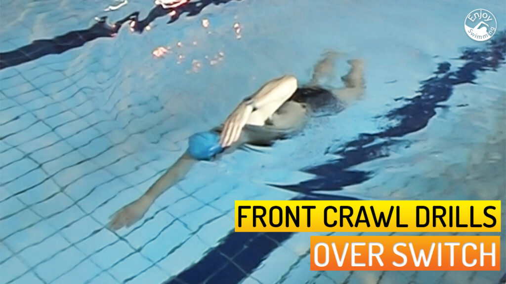 A novice swimmer who practices the over switch drill for the front crawl stroke.