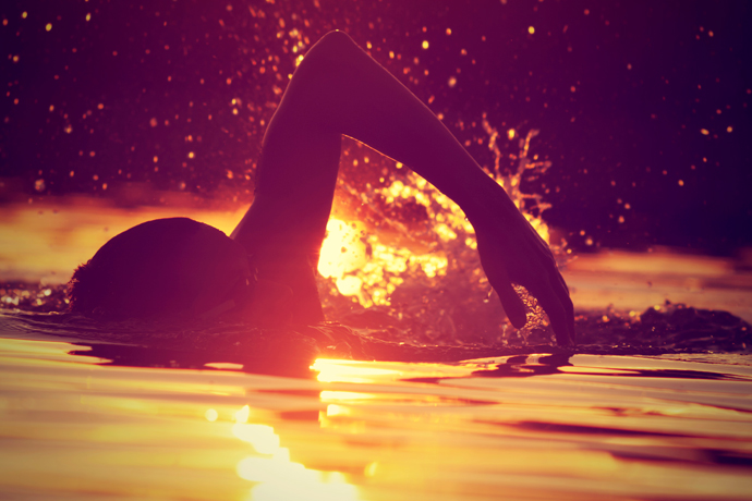 A front crawl swimmer with the setting sun reflected in the water in the background.