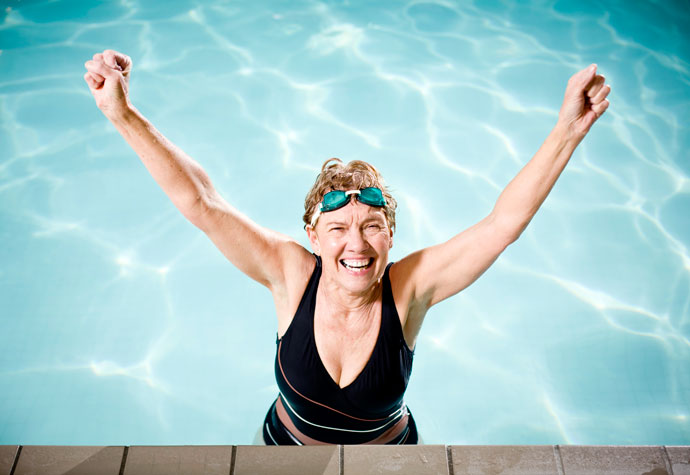 Health senior woman in a swimming pool and full of energy