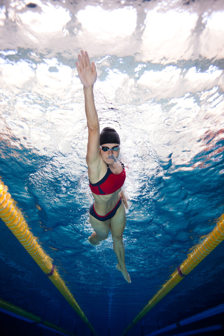 A female front crawl swimmer, with one arm nicely extended in front of her.