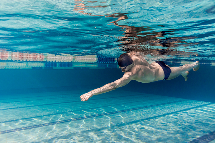 A young male front crawl swimmer is   engaging his core muscles to swim with more power.