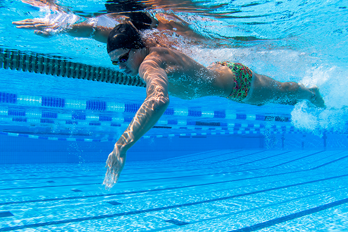 A young man swimming front crawl and using a high-elbow catch.