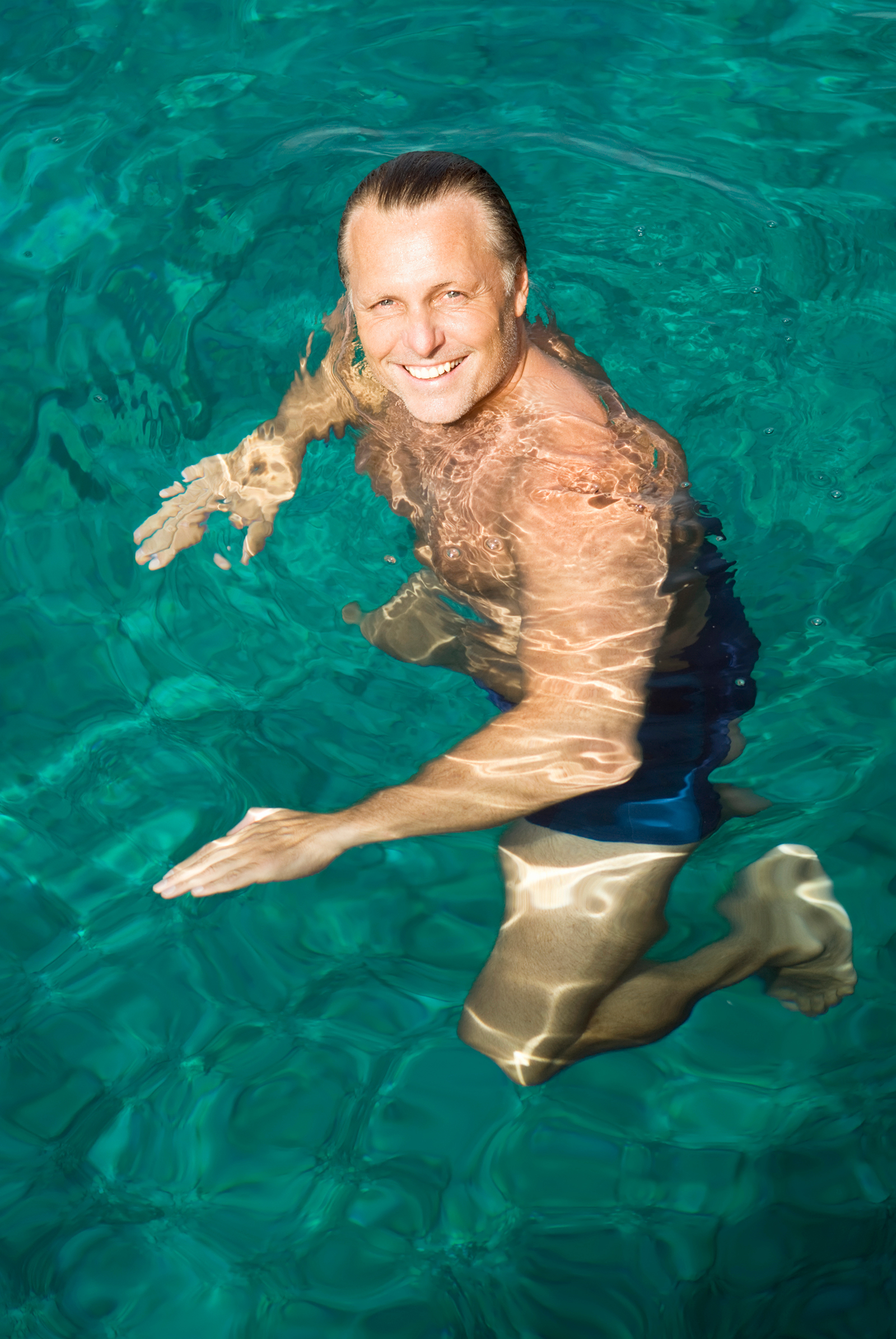 A man smiling while treading water.