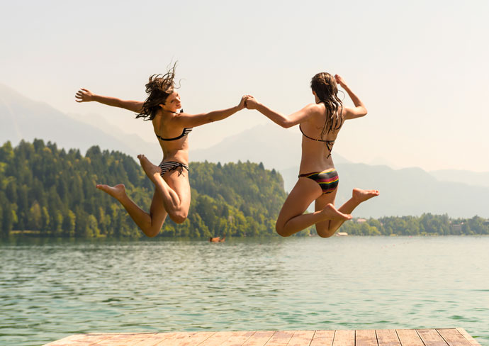 Two girls jumping into a lake