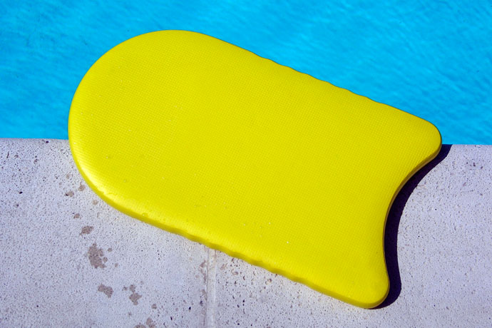 A kickboard lying on a pool's wall