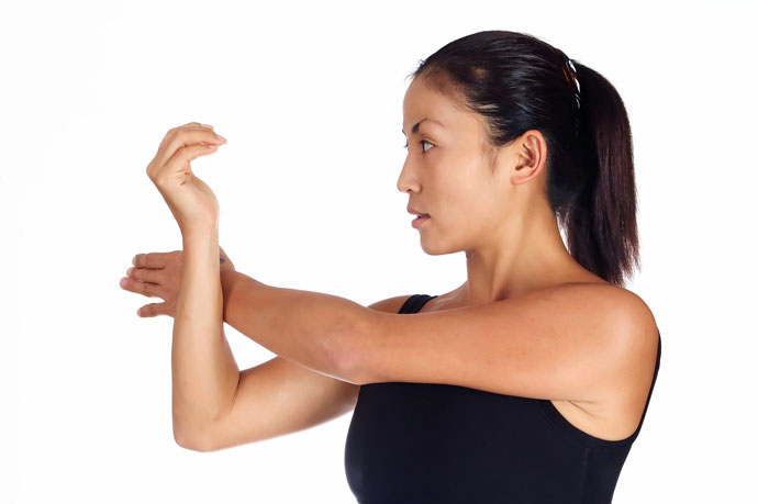 A woman stretching one of her shoulders