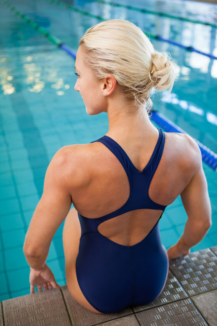 Focus on the back and shoulders of a well-toned female swimmer