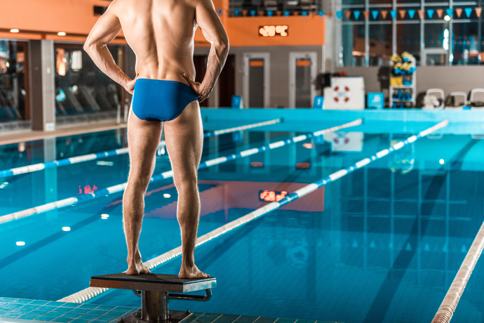 A swimmer in swimming trunks standing on a starting block