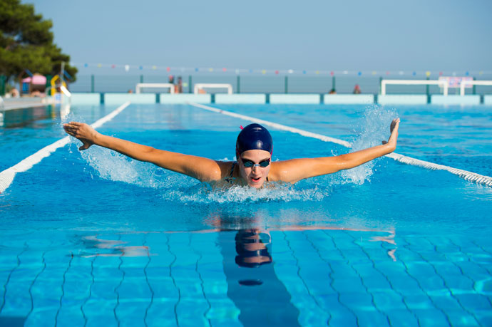A female butterfly stroke swimmer inhaling above water