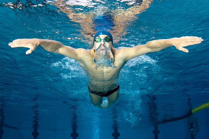 A butterfly stroke swimmer exhaling underwater