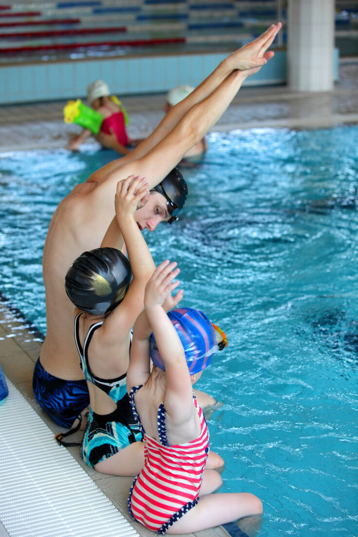 A swimming instructor teaches children how to dive.