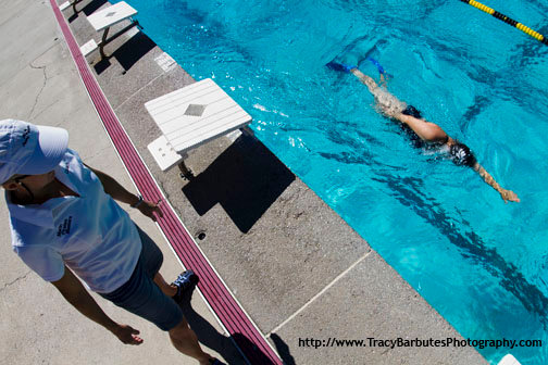 A swim instructor watching a student executing a swimming drill
