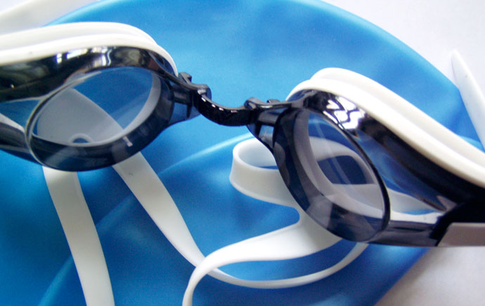 A pair of swimming goggles lying on a swim cap.