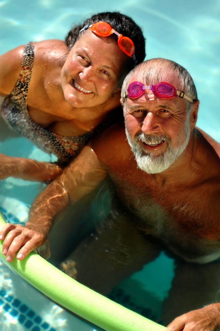 A happy elderly couple is relaxing in an outdoor pool on a sunny day.