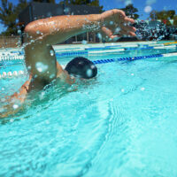 A front crawl swimmer swimming outside in an outdoor pool