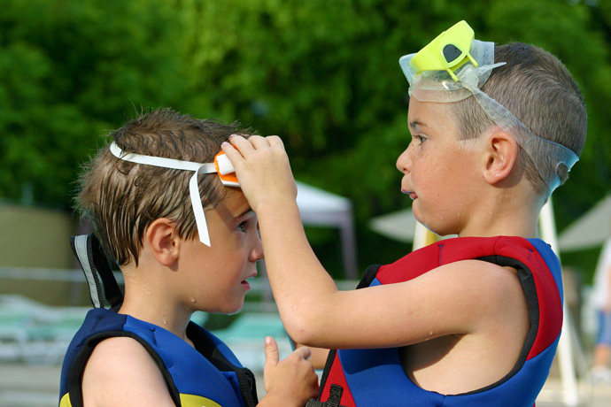 A young boy helps another young boy to put on swimming goggles.