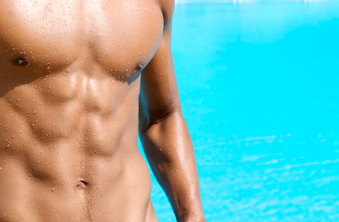 A lean muscular torso in the foreground and tropical blue water in the background