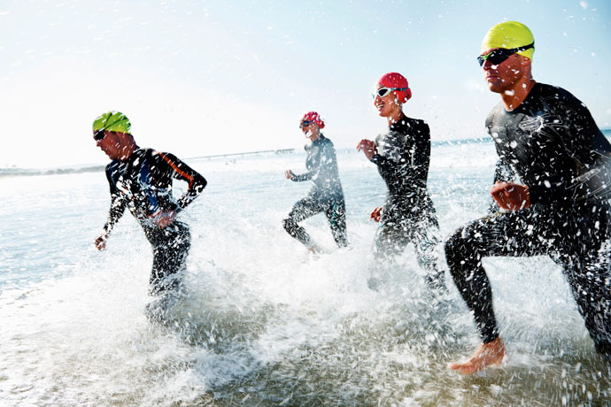 triathlon training - triathletes running toward the water