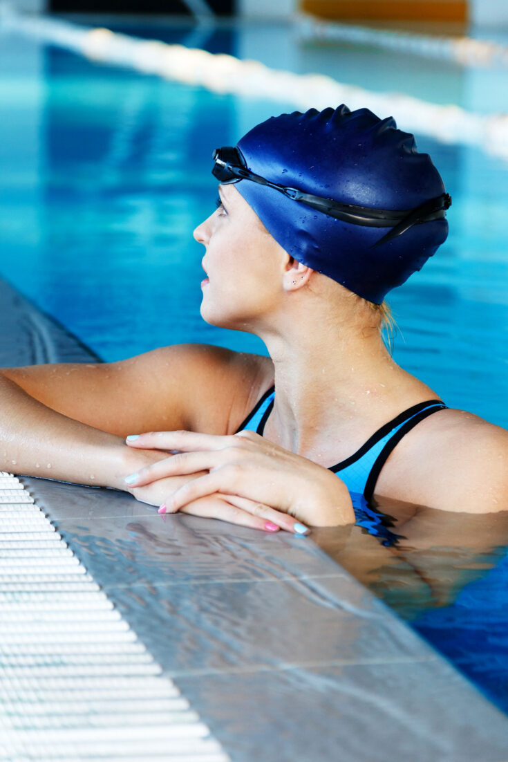 A young woman with a blue swimming cap resting at the edge of a swimming pool.